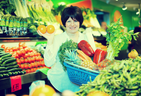 Smiling mature woman buying fresh fruits with basket on the market Stock Photo