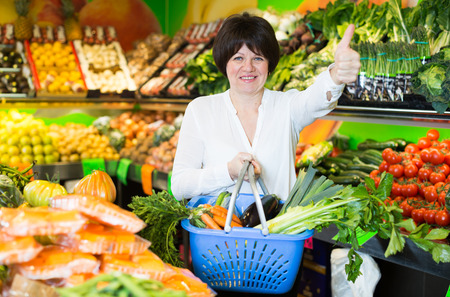 Adult cheerful female taking vegetables with basket on the store