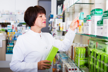 Cheerful woman druggist wearing white coat standing among shelves in pharmacy Stock Photo
