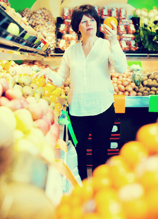 Middle aged smiling woman choosing fruits on the store Stock Photo