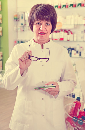 Portrait of diligent pleasant female druggist in white coat working in pharmacy