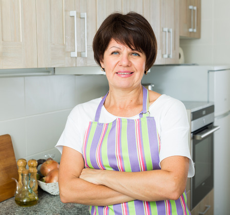 Portrait of glad mature woman housewife standing at kitchen indoors