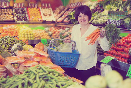 Mature woman buying fresh vegetables with basket on the market Stock Photo