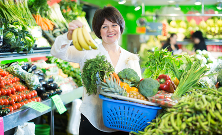 Mature woman buying fresh fruits and vegetables with basket on the market