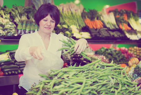 Adult cheerful female taking vegetables on the market Stock Photo