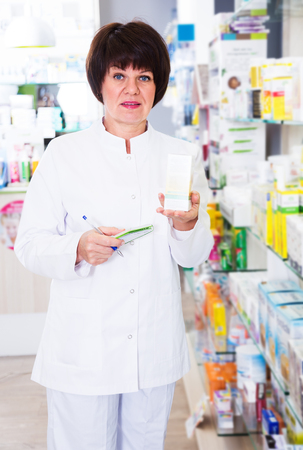 Positive woman druggist wearing white uniform standing among shelves in pharmacy