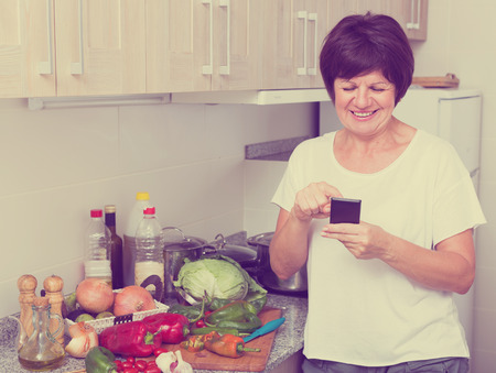Portrait of glad mature woman looking at mobile phone while making dish on kitchen at home Stock Photo