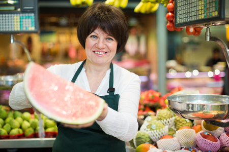 Mature woman offering watermelon and other fresh fruits on the market Stock Photo