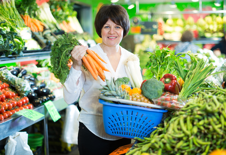 Smiling mature woman buying fresh vegetables with basket on the store Stock Photo