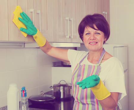 glad retiree woman cleaning surfaces at home using duster and household chemicals Stock Photo