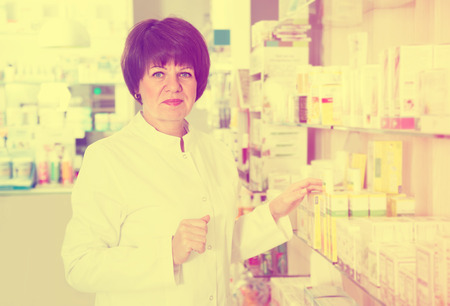 smiling woman pharmacist wearing uniform and working in pharmaceutical shop inside