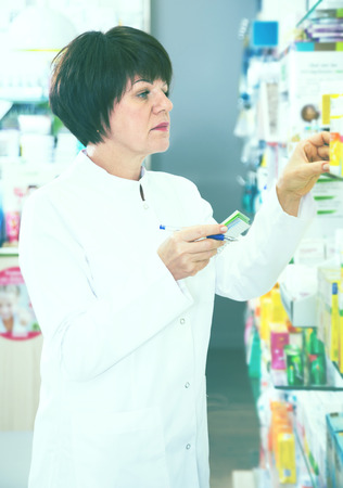 Positive woman druggist wearing white coat standing among shelves in drugstore Stock Photo