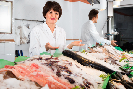 Two smiling sellers posing near display with frozen fish