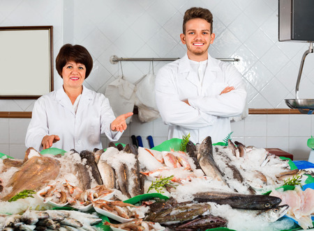 Two  positive smiling sellers posing near display with frozen fish