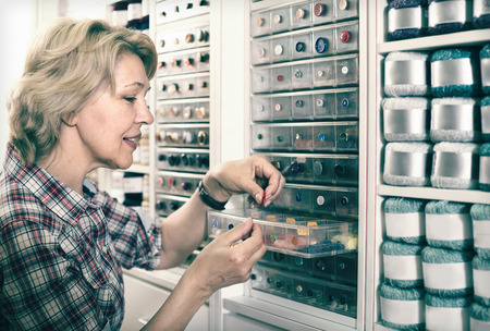 blonde mature housewife choosing various buttons in sewing store