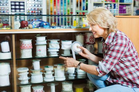 Mature glad woman customer picking various ribbon in sewing department