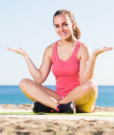 Cheerful young woman working out in beach outdoor