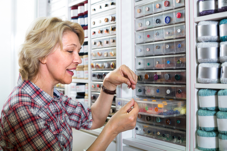 smiling blonde mature woman selecting various buttons in sewing store Stock Photo