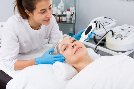 salon: Aged woman making beauty procedures for face in spa salon Stock Photo
