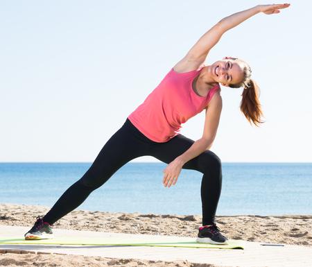Smiling girl in sportswear practice  yoga at sea beach