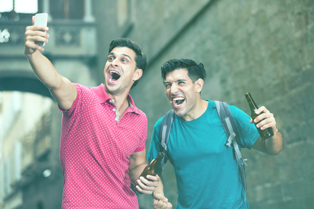 Men walking with beer are making selfie at city