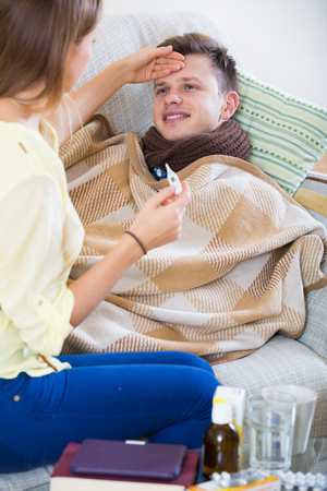 family sofa: Portrait of sick guy with flue and nursing girl indoors