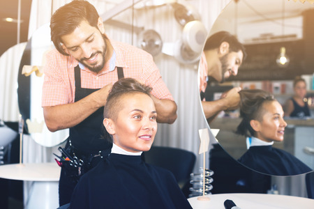 salon: Smiling male hair artist making hairstyle for woman visitor in salon Stock Photo