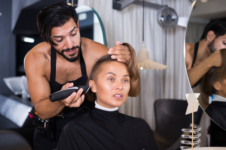 Positive sexy adult hairdresser working with hair clipper with woman Stock Photo