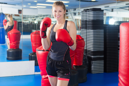 Portrait of woman boxer who is training in gym. Stock Photo