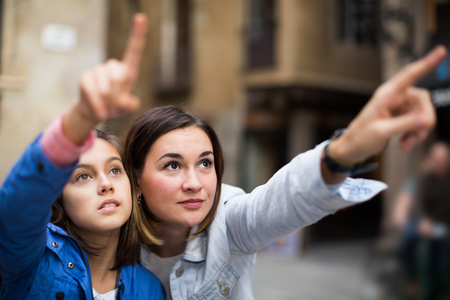 Happy mother pointing to daughter new sight during sightseeing tour