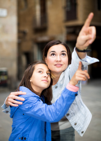Cheerful mother and daughter pointing at sight during sightseeing tour Stock Photo