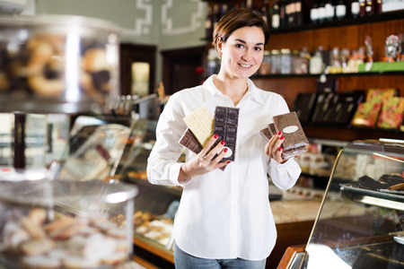 Smiling girl deciding on best bar of chocolate in confectionery