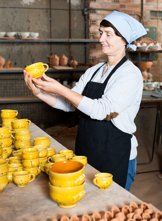 Cheerful mature master among the pottery at the workshop