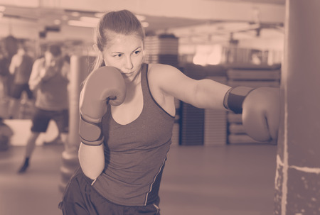 Portrait of young belorussian woman who is training in box gym.
