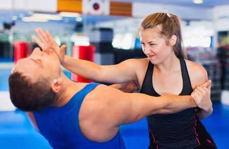 La mujer audaz positiva está entrenando con el hombre en el curso de defensa personal en el gimnasio. Foto de archivo