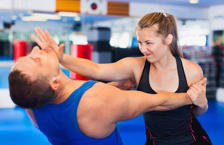 Bold positive  woman is training with man on the self-defense course in gym.
