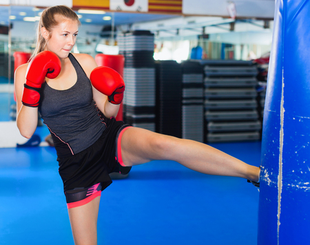 Cheerful positive smiling woman boxer is training kick in box gym.