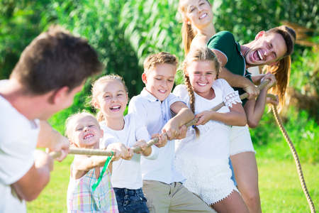 Group of laughing young people with kids having fun together outdoors pulling rope Stockfoto