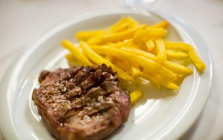 entrecote with potato chips on a plate, close up shot