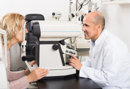 Senior mature and experienced male optician doing eye check up to smiling mature woman