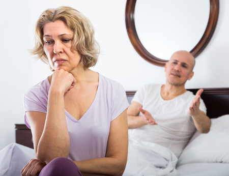 Frustrated mature wife and husband having serious conflict in bedroom
