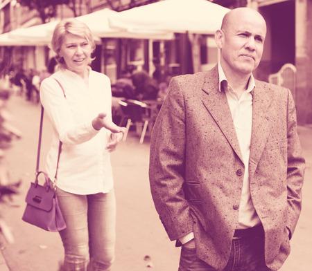 argumentation: irritated senior man standing back to annoyed woman outdoors