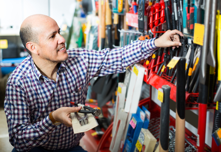 Ordinary senior man choosing tooking in household store Stock Photo