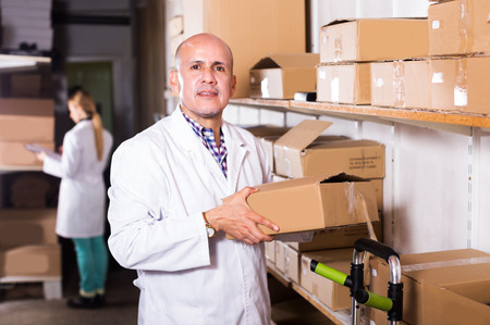 Adult man worker performing loading works in storage