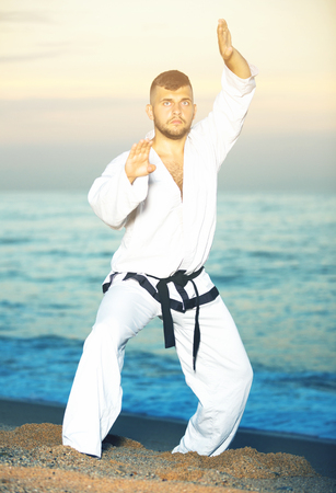 Adult man is practicing karate moves on the beach near the sea.