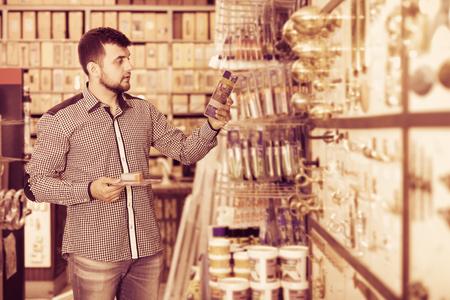 Happy man deciding on best glue in houseware store