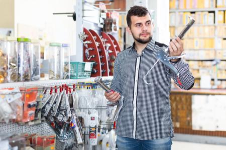happy male customer examining various glue guns in houseware store