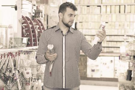 Glad adult man choosing new glue gun in houseware store Imagens - 86810500