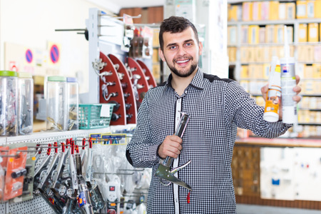 positive male customer examining various glue tubes in houseware store