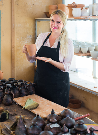 pretty female artisan having ceramics in hands and standing in workshop